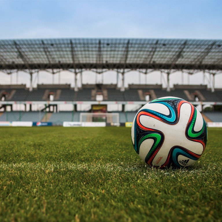 A soccer ball in the middle of a stadium field